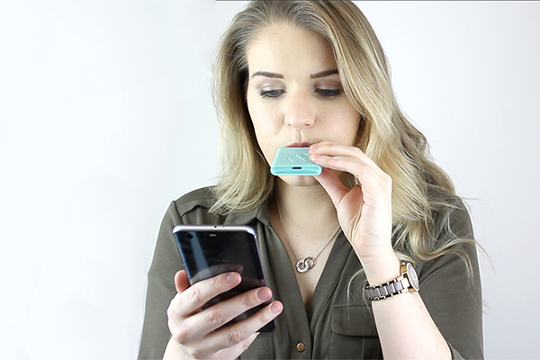 A woman does a hydrogen breath test with AIRE, a personal digestive tracker