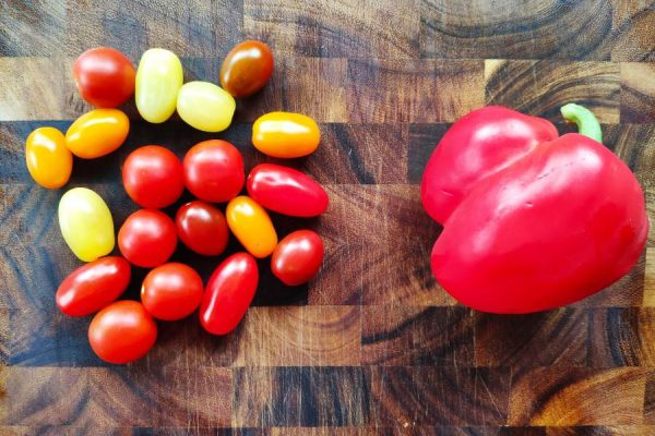 Red, yellow and orange tomatoes beside red pepper