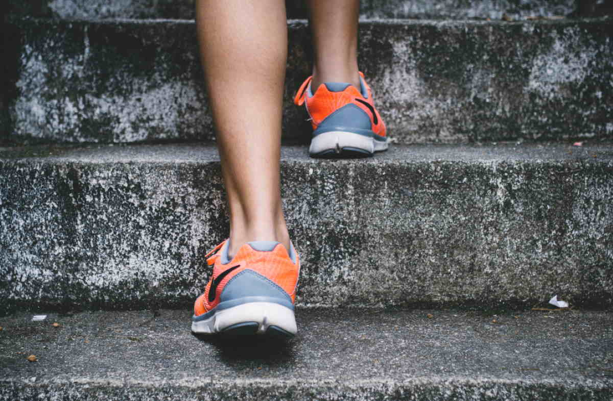 Person wearing running shoes walking up stairs
