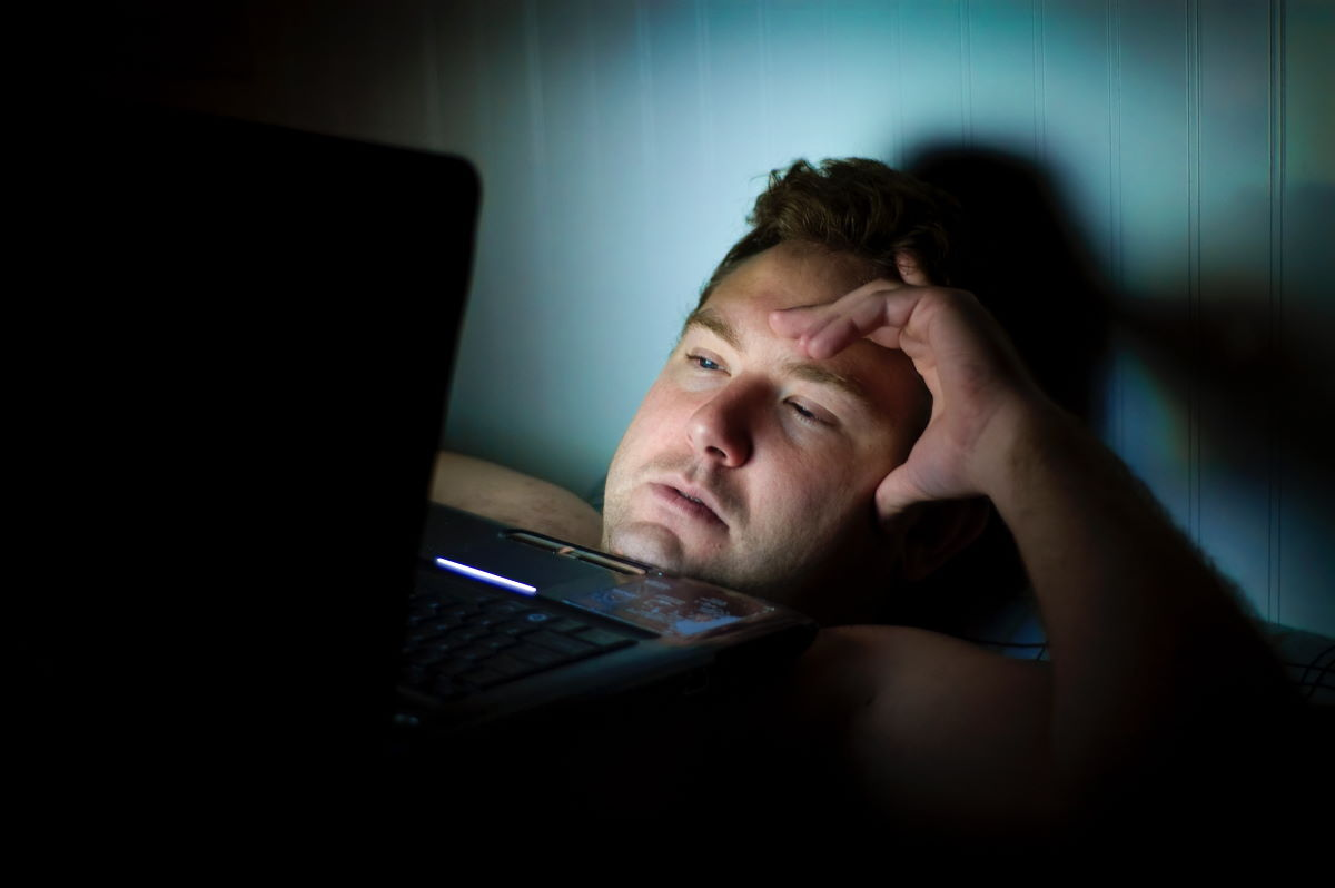 Man on laptop in bed