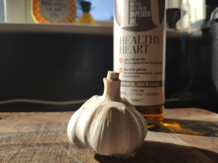 Close up of garlic bulb and bottle of oil