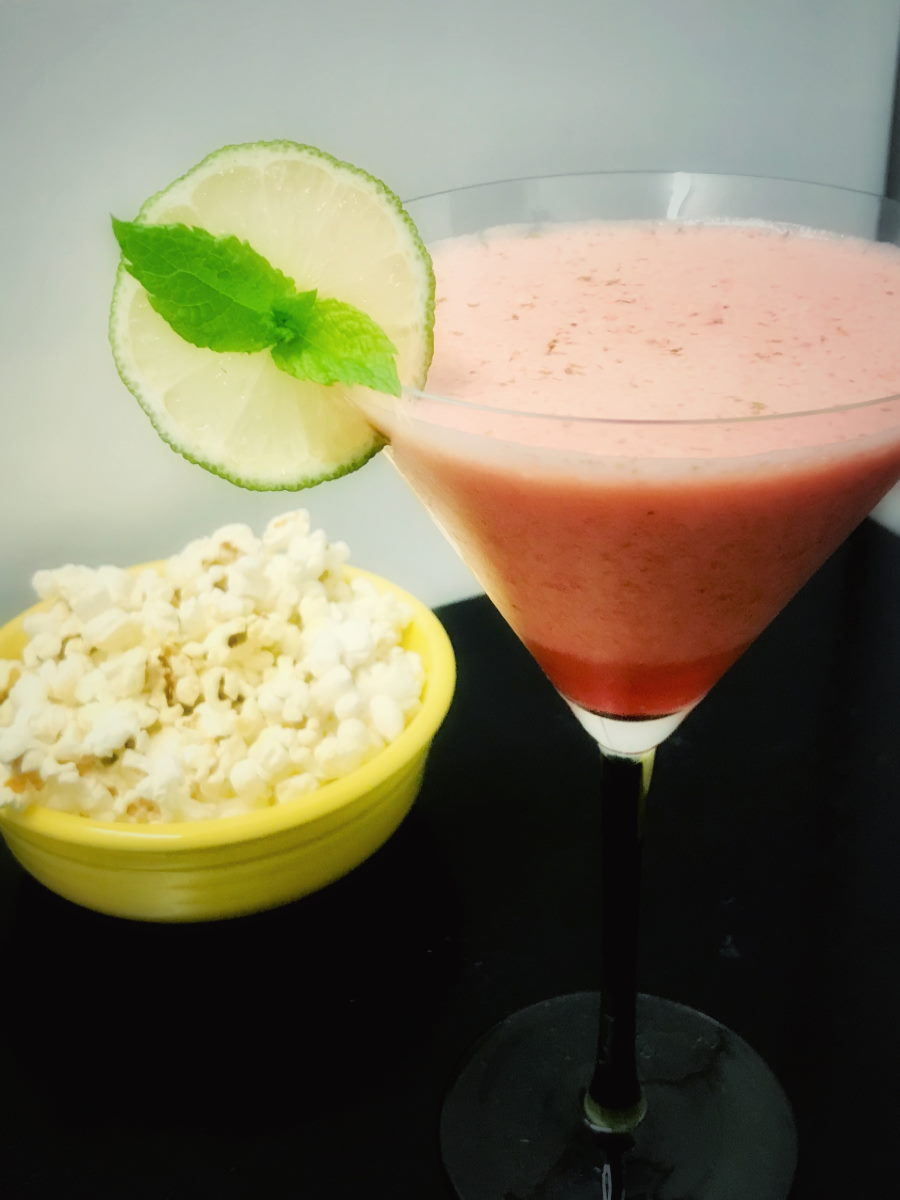 martini glass with strawberry sour and a bowl of popcorn beside it