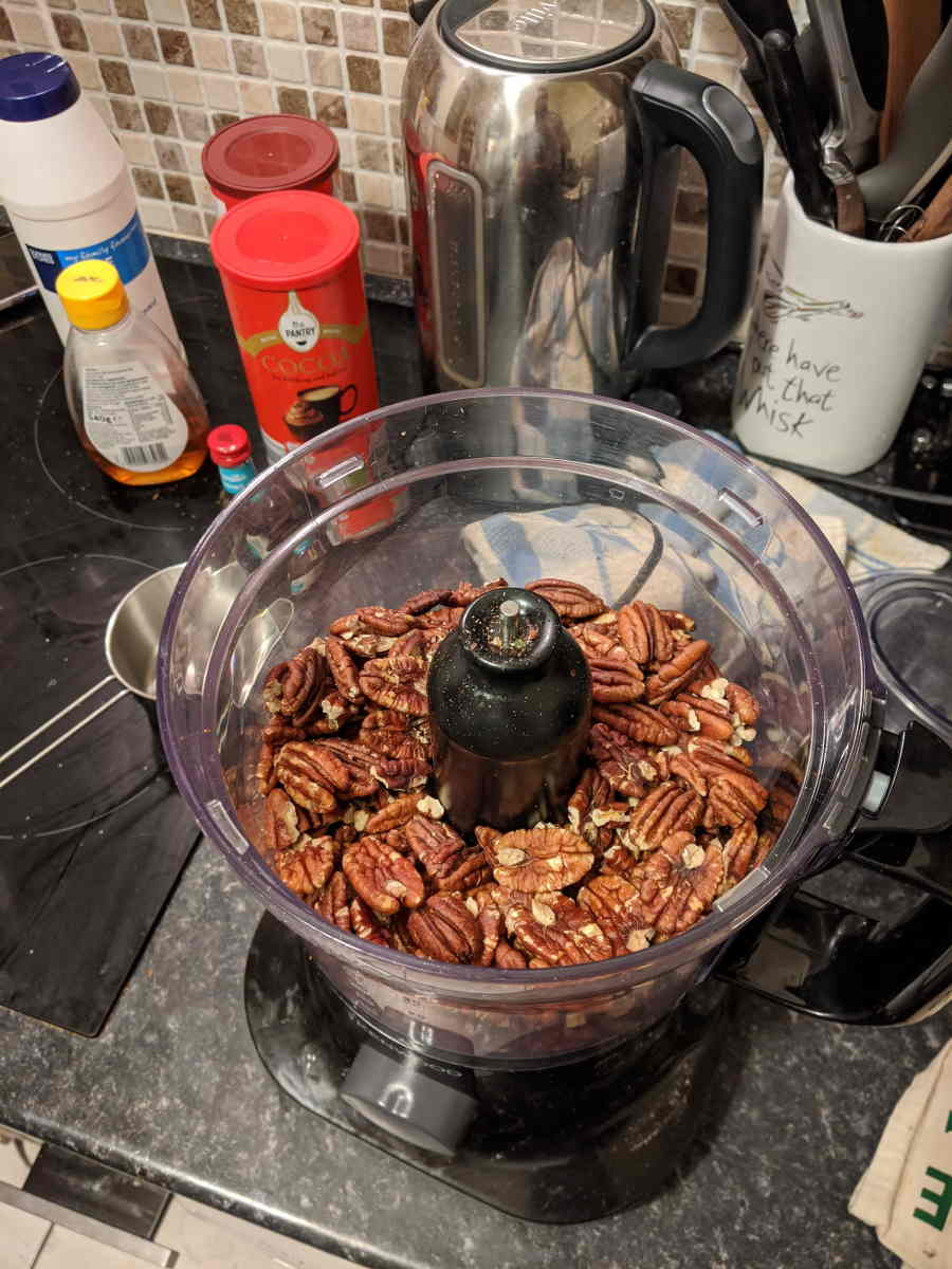 pecan nuts in blender before blended, with other ingredients in the background