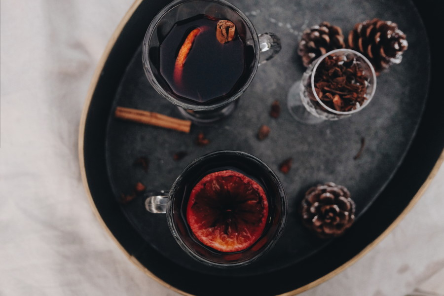 birds eye view of 2 glasses of mulled wine on black tray